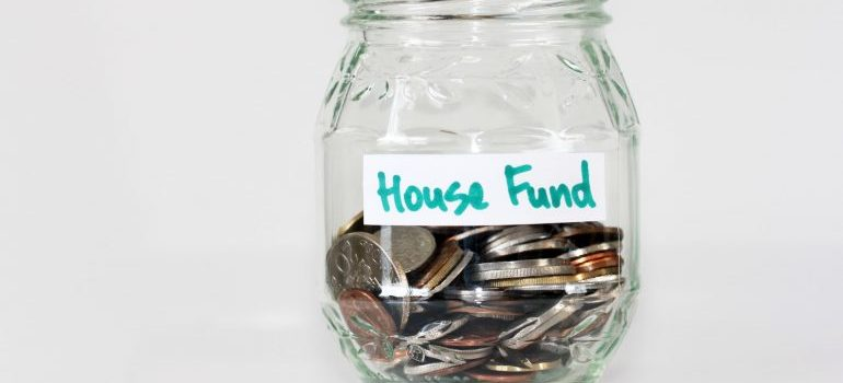 Coins in a house fund jar for saving money for moving out of your parents' home